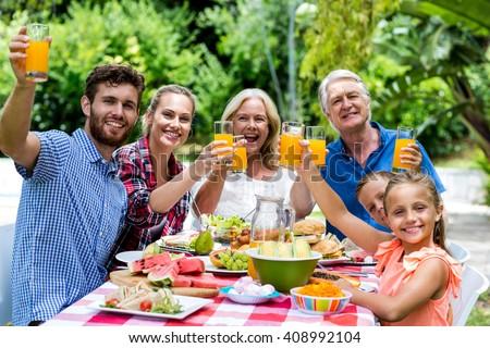 Happy family having breakfast at table in yard - stock photo