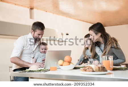 Happy family having breakfast , father on laptop with baby
