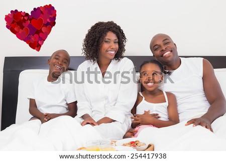 Happy family having breakfast in bed against heart - stock photo