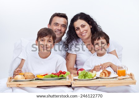 Happy family having breakfast in bed on a bright morning - stock photo