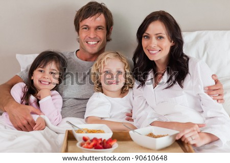 Happy family having breakfast together in a bedroom - stock photo