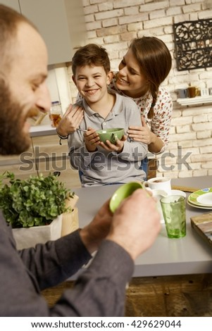 Happy family having breakfast together, mother hugging son. - stock photo