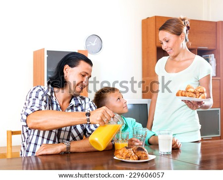 Happy family having breakfast with oranges juice in morning