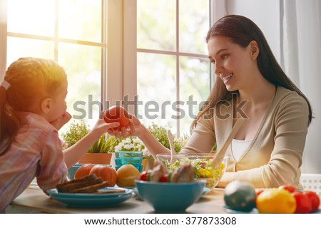 Happy family having dinner together sitting at the rustic wooden table. Mother and her daughter enjoying family dinner together. - stock photo