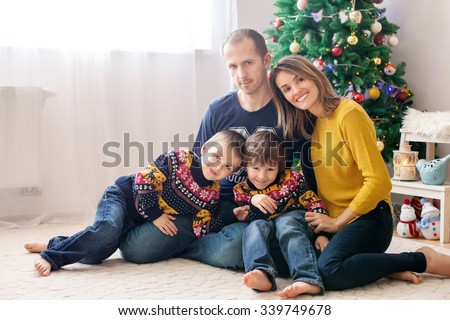 Happy family having fun at home, Christmas family portrait in front of the Christmas tree - stock photo