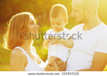 Happy family having fun. Baby boy with his mother and father looking at plastic bottle of water. Outdoor shot - stock photo