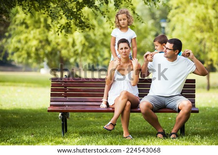 Happy family having fun in a park - stock photo