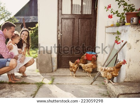 Happy family having fun in garden near the old farmhouse - stock photo