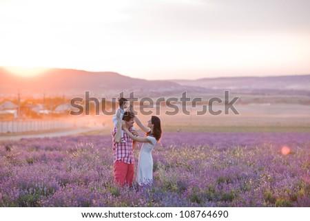 happy family having fun in lavender field - stock photo