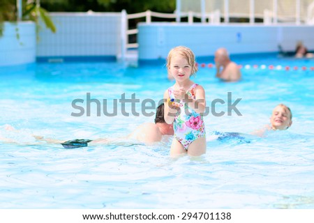 Happy family having fun in recreation swimming pool. Children enjoying day in waterpark during active summer holidays. Kids laughing and playing with waterguns. - stock photo
