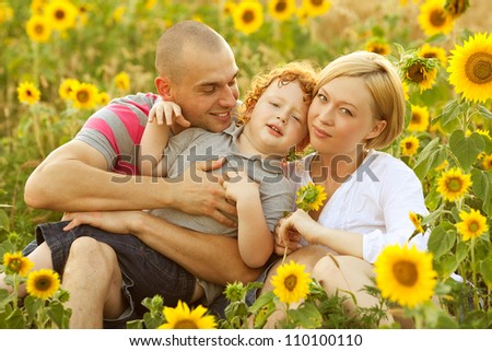 happy family having fun in the field of sunflowers. Father and mother hug their son. outdoor shot - stock photo