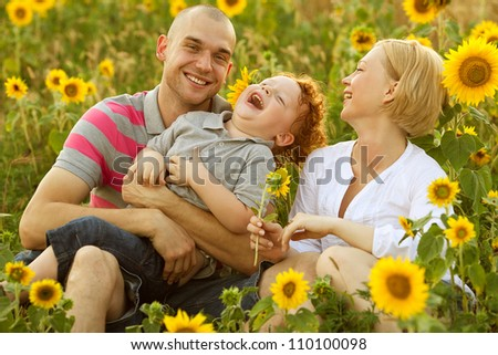 happy family having fun in the field of sunflowers. Father hugs his son. Mother holding sunflower. outdoor shot - stock photo
