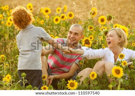 happy family having fun in the field of sunflowers. Son pulling his parents. outdoor shot - stock photo