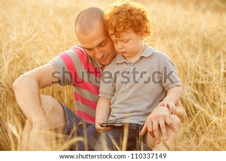 happy family having fun in the field with yellow flowers. Father hugs his son. dad and son looking at mobile device. outdoor shot