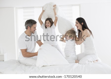 happy family having fun in the morning in parent's bed - stock photo
