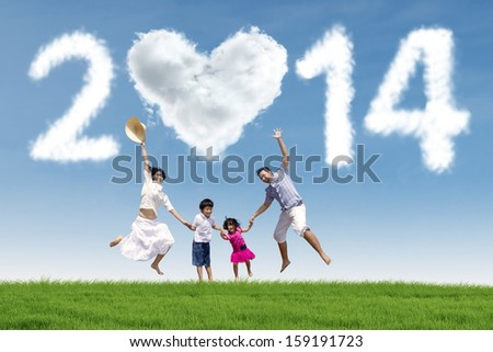 Happy family having fun in the park with heart shaped cloud of new year 2014