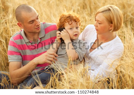 happy family having fun in the wheat field. Father and mother behind their son. Son calling on mobile (cell) phone. outdoor shot - stock photo
