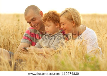 happy family having fun in the wheat field. Father and mother behind their son. Son watching something in dad's mobile (cell) phone. outdoor shot
