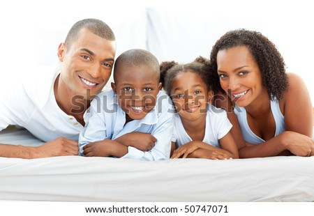 Happy family having fun lying down on bed at home - stock photo