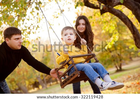 Happy family having fun on a swing ride at a garden a autumn day - stock photo