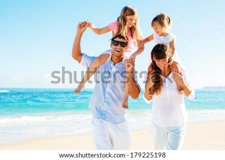 Happy family having fun on the beach - stock photo