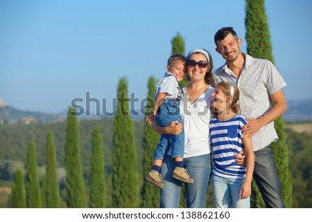 Happy family having fun on vacations in Tuscan against cypress alley background