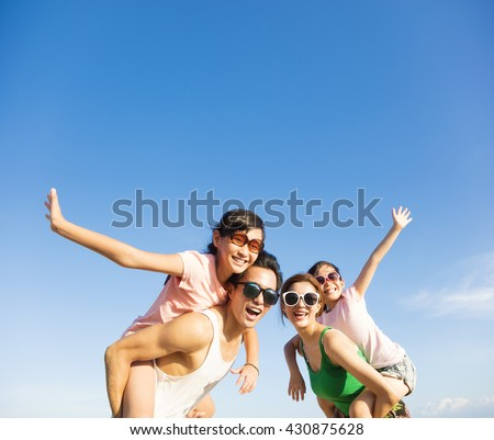 happy family having fun outdoors against blue sky background - stock photo