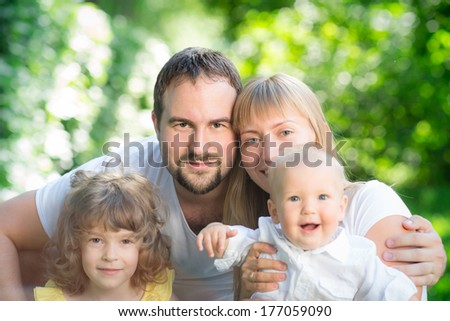 Happy family having fun outdoors against spring green background - stock photo