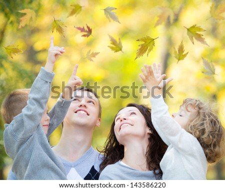 Happy family having fun outdoors in autumn park against blurred leaves background - stock photo