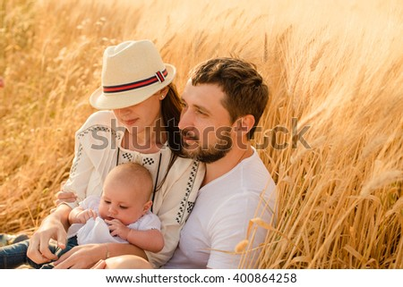 Happy family having fun outdoors in spring field - stock photo