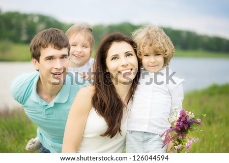 Happy family having fun outdoors in spring field against green background - stock photo
