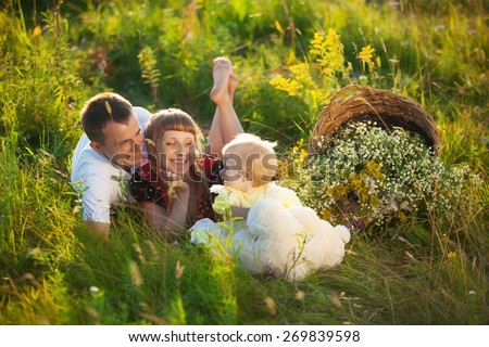 Happy family having fun outdoors in summer meadow. Father, mother and little child lying on grass. Family concept. Picnic. Man, woman and little girl together outside. Laughing, smiling people - stock photo