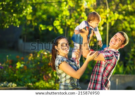Happy family having fun outdoors in summer. Mother, father and their cute baby-girl are playing in the sunny garden. Happy parenthood and childhood concept.  - stock photo