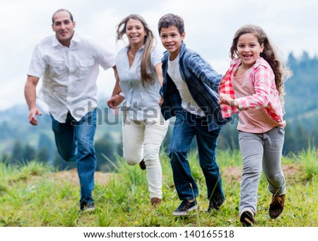 Happy family having fun outdoors running and holding hands - stock photo