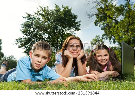 Happy family having fun outdoors with a laptop computer - stock photo