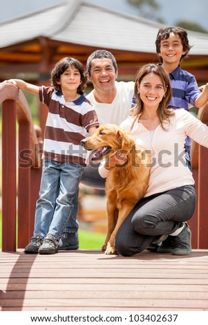 Happy family having fun outdoors with their dog