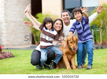 Happy family having fun outside their house - stock photo