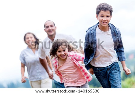 Happy family having fun racing at the park - stock photo