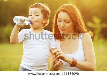 happy family having fun. son drinking water from the plastic bottle, mother holding his hands. outdoor shot. - stock photo