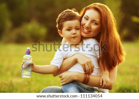 happy family having fun. son holding a bottle of water and smiling mother holding him in her arms. outdoor shot.