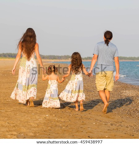 Happy family having fun together at sunset on the beach. Family look.