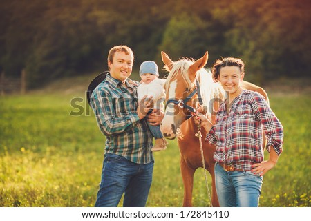 Happy family having fun with horses outdoors on green field on summer day  - stock photo