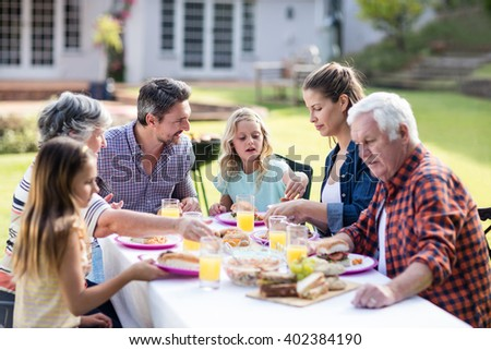 Happy family having lunch in the garden on a sunny day - stock photo