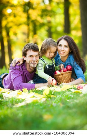 Happy family having picnic against blurred autumn leaves background - stock photo
