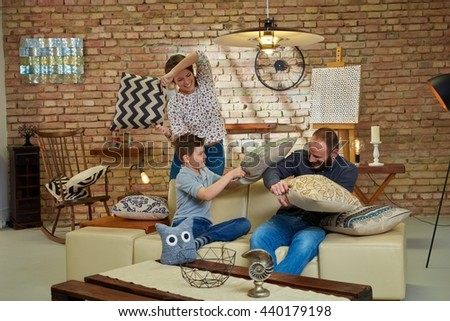 Happy family having pillow fight at home, having fun. - stock photo