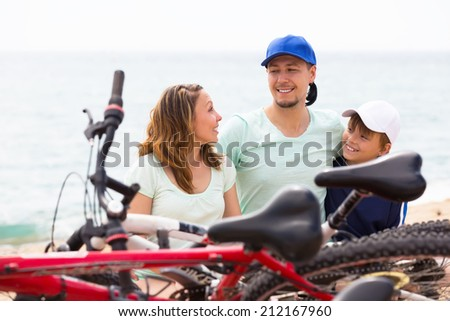 Happy family having rest after cycling on the beach - stock photo