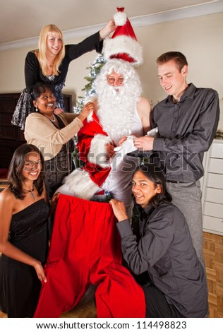 Happy family helping their father getting dressed in his santa claus costume