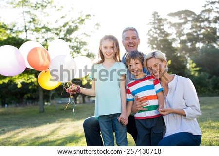 Happy family holding balloons at the park on a sunny day