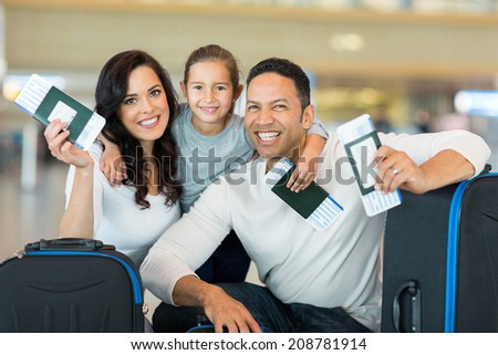 happy family holding boarding pass and passport at airport - stock photo