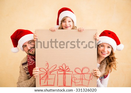 Happy family holding Christmas poster blank. Xmas holiday concept - stock photo
